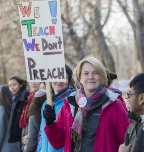 عدهای از معترضان مونترالی در مخالفت با قانون ۲۱ به خیابان آمدهاند. روی تابلو نوشته شده «ما آموزش میدهیم، موعظه نمیکنیم» / Graham Hughes / THE CANADIAN PRESS
